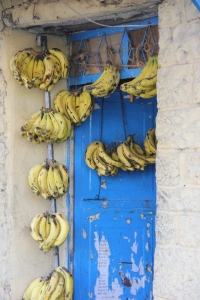 "Bananas for sale in the doorway of a local ""convenience store."""